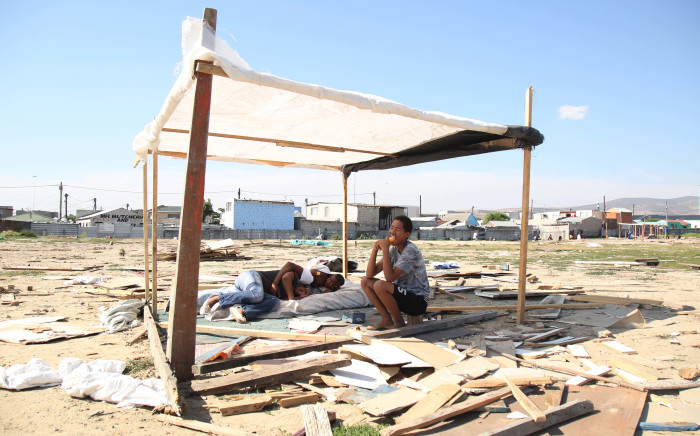 A Dunoon family sit under their half built structure after metro police broke down their previous home for the third time this year. Picture: Bertram Malgas