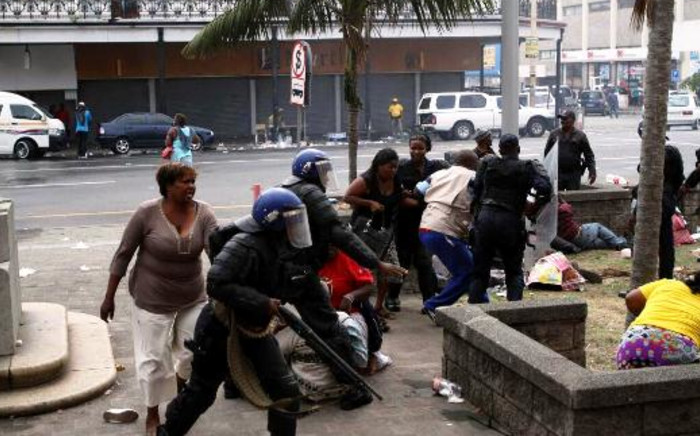 Police attempt to control a violent crowd of striking Samwu workers outside the East London City Hall. Protestors allegedly petrol bombed the building, setting it alight. Picture: Daily Dispatch via Twitter.