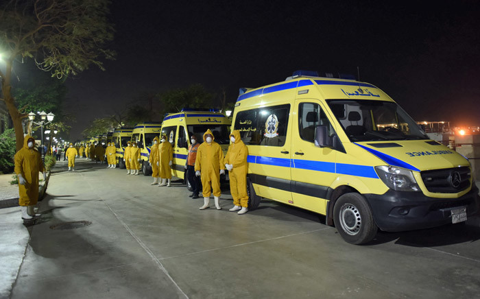 Egyptian health ministry emergency responders stand next to ambulances ready on the scene to transport suspected COVID-19 coronavirus disease cases that were detected on a Nile cruise ship, in the southern city of Luxor late on 7 March 2020. Picture: AFP