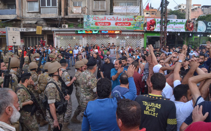 Lebanese army soldiers stand before anti-government protesters during a demonstration in Beddawi town on the outskirts of the northern Lebanese port city of Tripoli on 26 October 2019. Picture: AFP