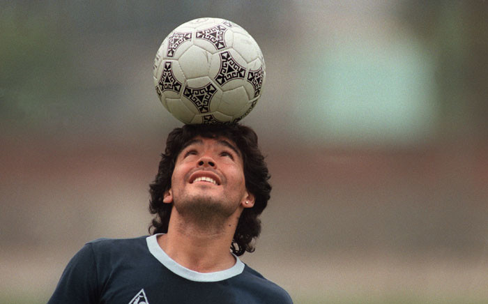 FILE: Argentine soccer star Diego Maradona balances a soccer ball on his head as he walks off the practice field following the national selection's 22 May 1986 practice session in Mexico City. Picture: AFP.