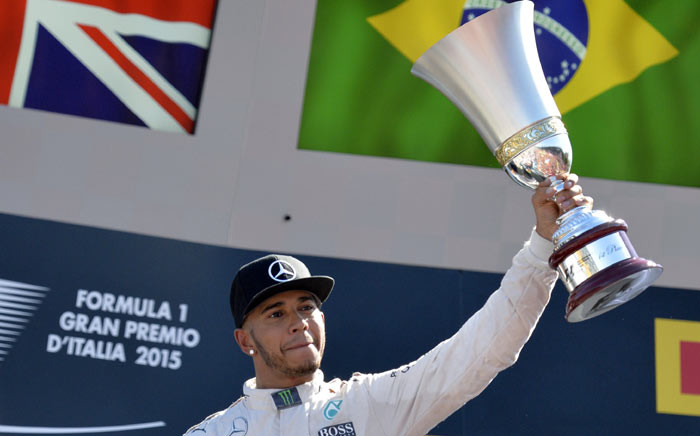 Mercedes AMG Petronas F1 Team's British driver Lewis Hamilton celebrates with his trophy on the podium after winning the Italian Formula One Grand Prix at the Autodromo Nazionale circuit in Monza on 6 September 2015. Picture: AFP