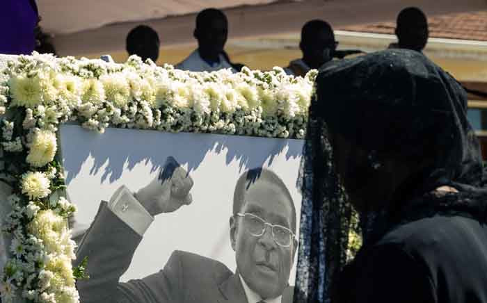 Former first lady Grace Mugabe walks past a portrait of Robert Mugabe during the burial of the former Zimbabwe leader at his home village in Kutama, on 28 September 2019. Picture: AFP