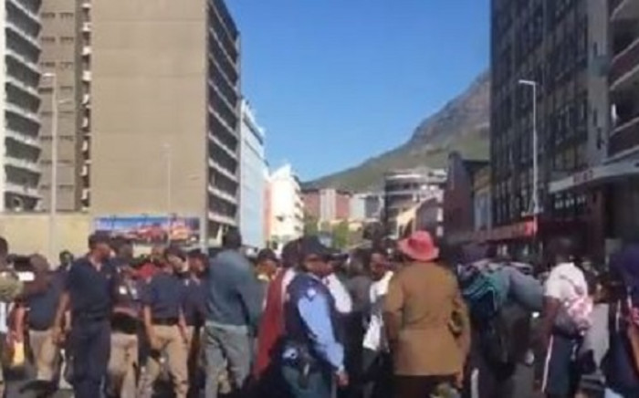 Law enforcement and SAPS are still surrounding the St Mary's Cathedral as the refugee group watches on, sitting on the pavement. The mattresses and other belongings left around the church are also being cleaned out. Picture: Jarita Kassen/EWN