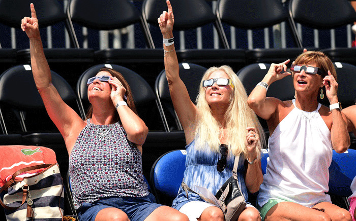 Fans watch the solar eclipse during the third day of the Winston-Salem Open at Wake Forest University on 21 August 2017 in Winston Salem, North Carolina. Picture: AFP