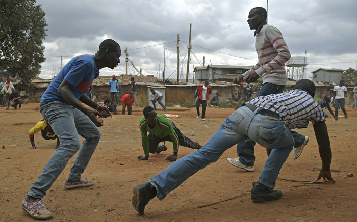 FILE: Protesters duck to avoid live bullets from riot police in the Kibera slum in Nairobi on 12 August 2017. Picture: AFP.