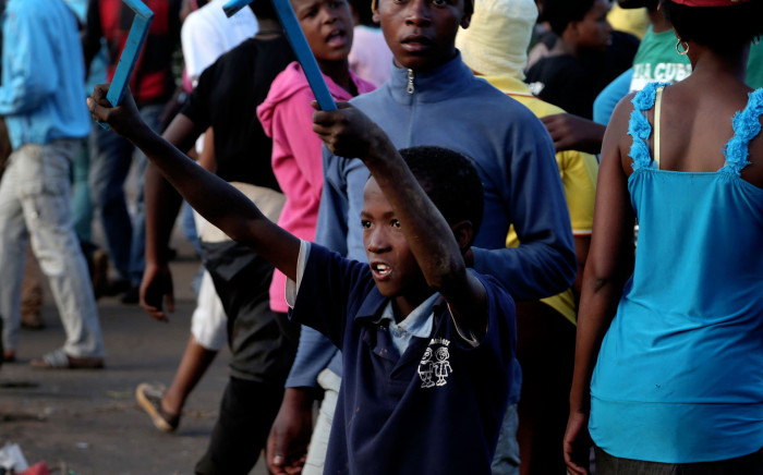 A young boy holding metal rods as weapons taunts the police during a violent service delivery protest. Picture: Sebabatso Mosamo/EWN.
