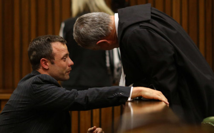 Oscar Pistorius cries as he speaks to his lawyer Barry Roux during his trial at the High Court in Pretoria on 10 March 2014. Picture: Pool.