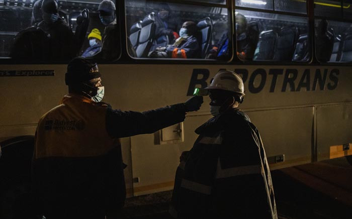 A mine employee measures the temperature of a mine worker, en route to his evening shift at the Sibanye-Stillwater platinum mine, before letting him board a company bus at the Wonderkop taxi rank in Marikana, near Rustenburg, on 15 May 2020. Picture: AFP.