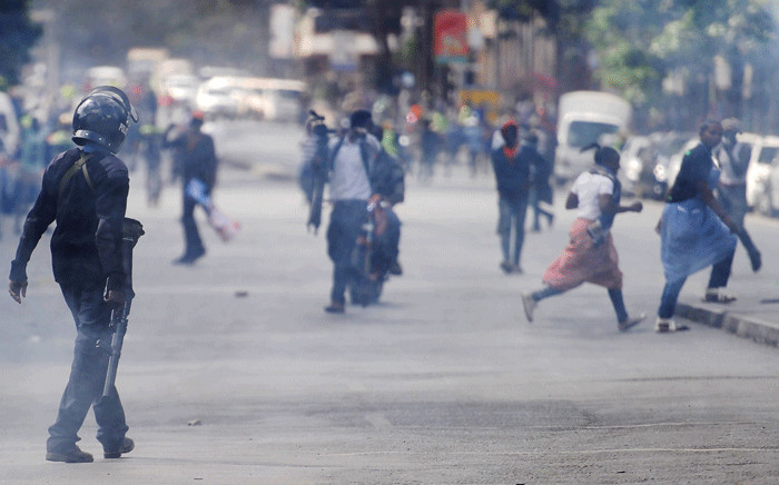 A police officer walks through a cloud of teargas in Kenya to disperse supporters of the National Super Alliance (NASA) in Nairobi on 11 October 2017. Picture: AFP