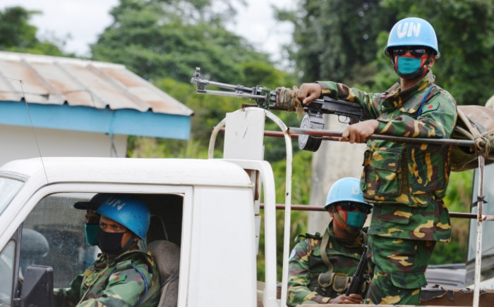 Soldiers of UNOCI (United Nations Operation in Cote d'Ivoire) wear a face mask to protect themselves from the Ebola virus as they patrol in Kandopleu, on 14 August 2014 near Biankouma near the border with Guinea and Liberia. Picture: AFP.