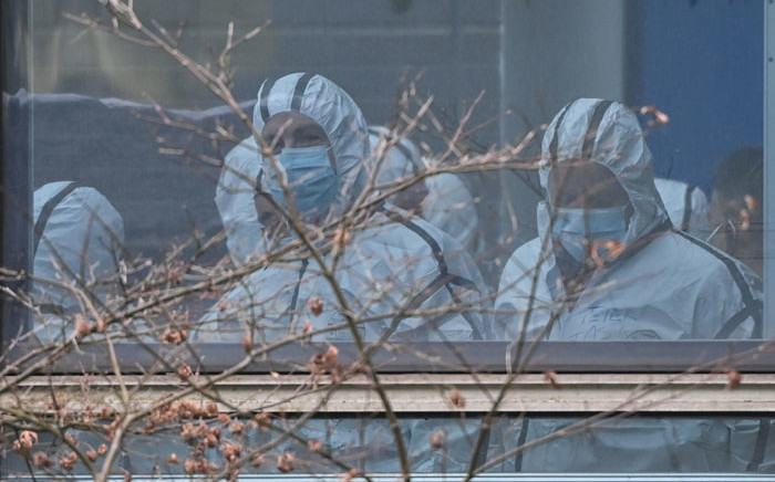 Members of the World Health Organization (WHO) team investigating the origins of the COVID-19 coronavirus, wearing protective gear are seen during their visit to the Hubei Center for animal disease control and prevention in Wuhan, China's central Hubei province on 2 February 2021. Picture: Hector Retamal/AFP