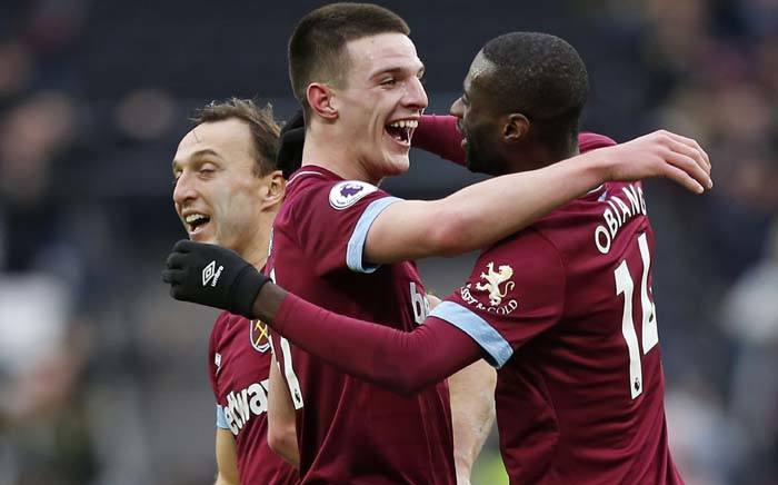 FILE: West Ham United's Irish defender Declan Rice (C) and West Ham United's Spanish midfielder Pedro Obiang (R) embrace as West Ham players celebrate on the pitch after the English Premier League football match between West Ham United and Arsenal at The London Stadium, in east London on 12 January 2019. West Ham won the game 1-0. Picture: AFP