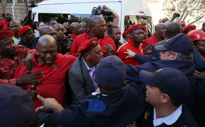 Policemen break up a scuffle between EFF MPs and ANC members at Parliament in Cape Town on Thursday, 21 August 2014. Picture: Sapa.