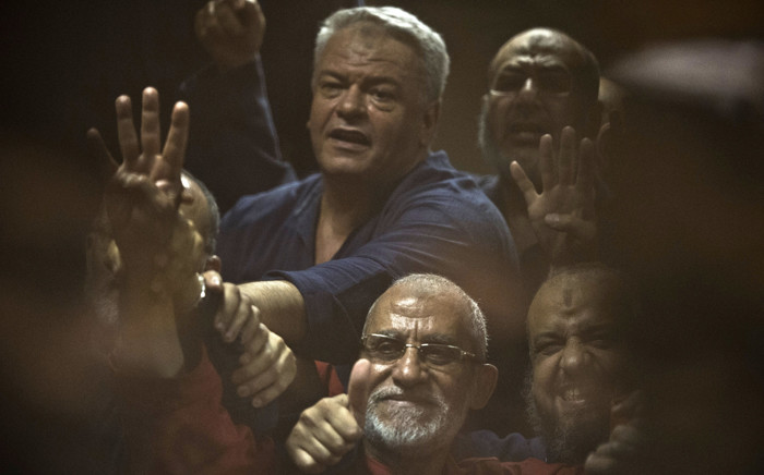 FILE: Egyptian Muslim Brotherhood leader Mohamed Badie (C-bottom) gestures from behind the defendant's cage as he attends his trial, along with ousted Islamist president Mohamed Morsi (unseen) in Cairo on 16 June 2015. Picture: AFP