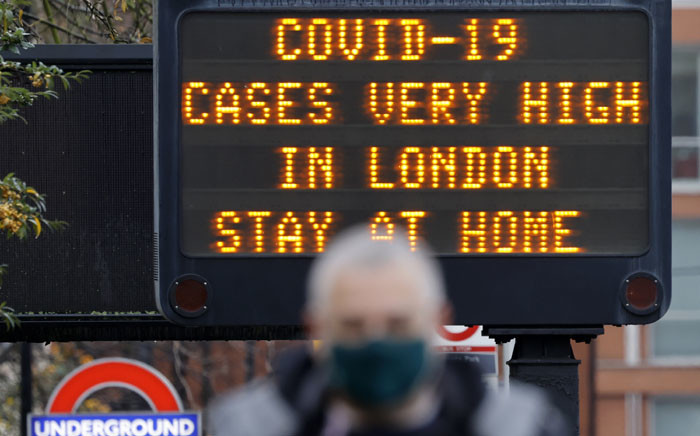 """FILE: In this file photo taken on 23 December 2020, a pedestrian walks past a sign alerting people that """"COVID-19 cases are very high in London - Stay at Home"""", in central London. Picture: AFP"""