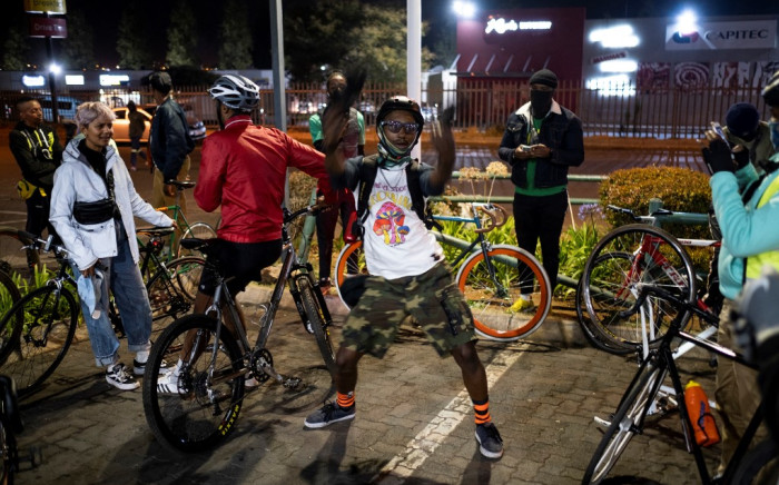 """A member of the Biking Bandits dances while they take a break during the """"Homies Night Ride"""" in Soweto on June 24, 2021. The Biking Bandits, a Soweto-based cycling crew, hosted a """"Homies Night Ride."""" This is an evening cycling route through the streets of Soweto. Not only is it good fun and exercise, but it is also """"a political statement,"""" according to co-founder Tiyiselani Mashele, as it is a way to create visibility of black people on bicycles, reclaiming the streets. Picture: AFP."""