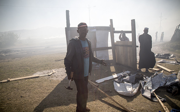 FILE: A resident of Parkwood in Cape Town rebuilds his demolished shack. Picture: Thomas Holder/EWN.