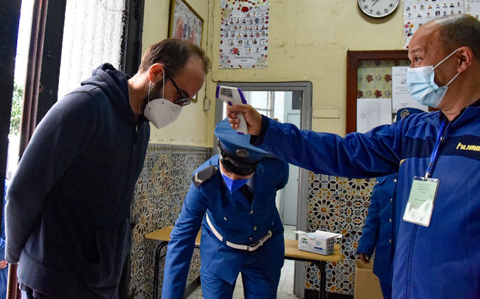 An Algerian man gets his temperature checked as a measure of precaution against the COVID-19, before voting at a polling station in the capital Algiers during a vote for a revised constitution, on 1 November 2020. Picture: AFP