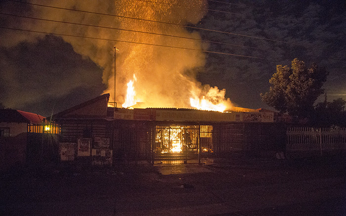Flames rise from two shops set alight during overnight looting in Mabopane north of Pretoria on 21 June 2016. Picture: Reinart Toerien/EWN.
