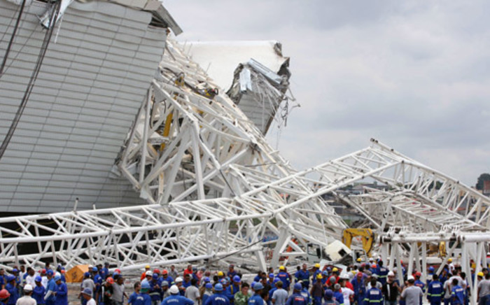 Workers examine the damage after a crane fell across part of the metallic structure at the Itaquerao stadium under construction in Sao Paulo. Picture: AFP.