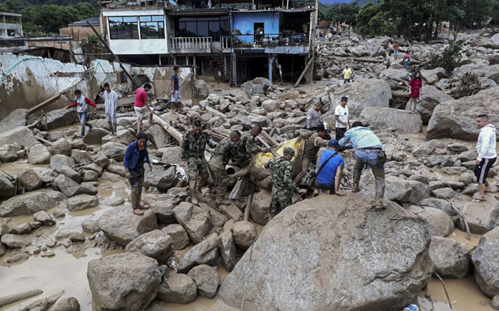 Handout picture released by the Colombian Army press office showing soldiers carrying a corpse following mudslides caused by heavy rains, in Mocoa, Putumayo department, on 1 April 2017. Mudslides in southern Colombia -caused by the rise of the Mocoa River and three tributaries- have claimed at least 16 lives and injured some 65 people following recent torrential rains, the authorities said. Picture: AFP