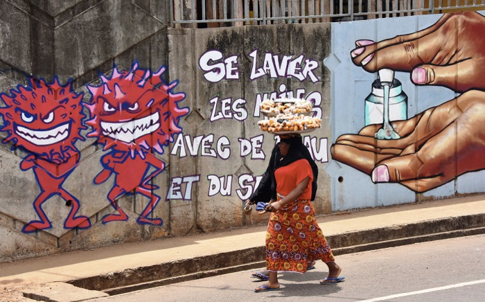 A woman walks past graffiti on a wall depicting hygiene measures to curb the spread of the COVID-19 coronavirus in Conakry, Guinea, on 4 May 2020. Picture: AFP