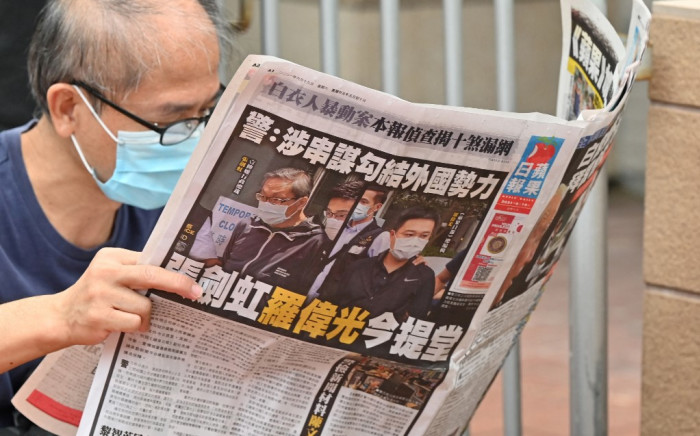 """This file photo taken on June 19, 2021 shows a supporter reading a copy of the Apple Daily newspaper outside a court in Hong Kong, after the two Apple employees were charged with collusion over their newspaper's coverage after authorities deployed a sweeping security law. Hong Kong's pro-democracy newspaper Apple Daily will print its final edition """"no later than Saturday"""", bosses confirmed on June 23, 2021, after police froze accounts and arrested staff using a new national security law. Peter PARKS / AFP"""
