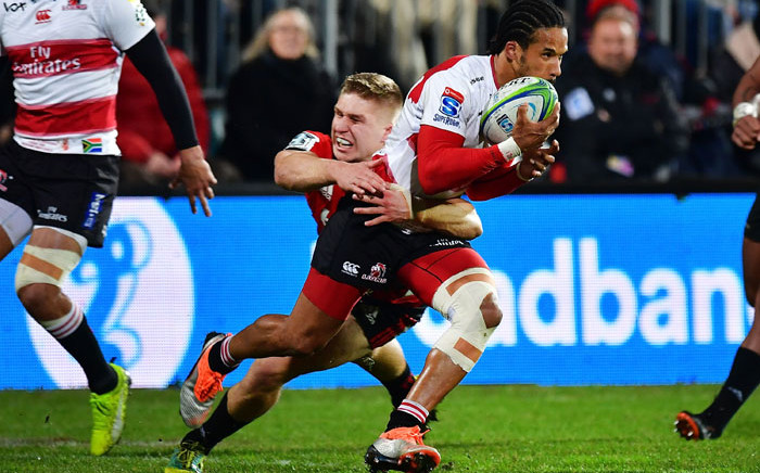 FILE: The Lions' Courtnall Skosan (centre R) is tackled by the Crusaders' Jack Goodhue (centre L) during the Super Rugby final match between the Crusaders and the Lions at AMI Stadium in Christchurch on 4 August, 2018. Picture: AFP