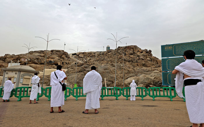 Muslim pilgrims pray next to Saudi Arabia's Mount Arafat, also known as Jabal al-Rahma (Mount of Mercy), southeast of the holy city of Mecca, during the climax of the Hajj pilgrimage amid the COVID-19 pandemic, next to 19 July 2021. Picture: Fayez Nureldine/AFP