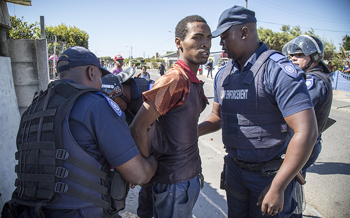 A protester in Parkwood is arrested by law enforcement for public violence. Picture: Thomas Holder/EWN.