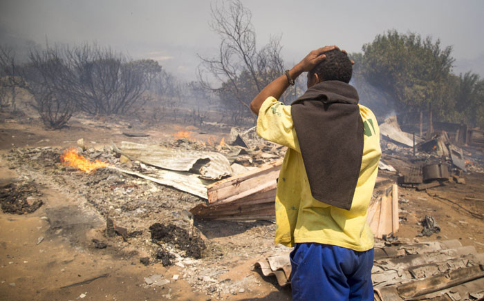 Ocean View resident Elroy-Ricardo Isaacs looks at the smouldering ruins of his home on 11 January 2016. Picture: Aletta Harrison.