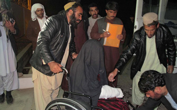 A wounded Afghan woman (C) is brought to the hospital in Helmand province early on 1 January, 2015 after a rocket fired during fighting between Afghan forces and insurgents killed at least 15 wedding guests late on 31 December. Picture: AFP