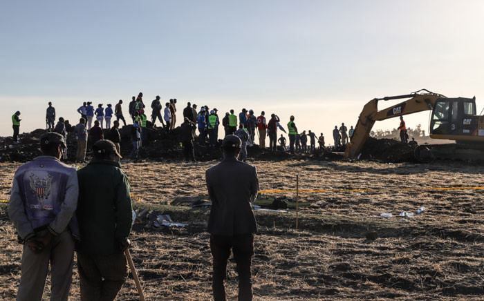 People watch workers at the crash site of a Nairobi-bound Ethiopian Airlines flight near Bishoftu, a town some 60 kilometres southeast of Addis Ababa, Ethiopia, on 10 March 2019. Picture: AFP