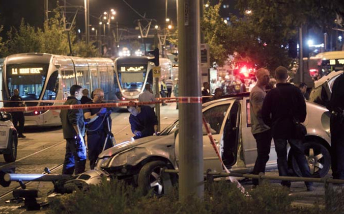 Israeli police examine a car at the scene of what is believed to be an terrorist attack in Jerusalem, on 22 October 2014. According to Israeli police a Palestinian driver slammed his car into a Jerusalem light rail train station. Picture: EPA.