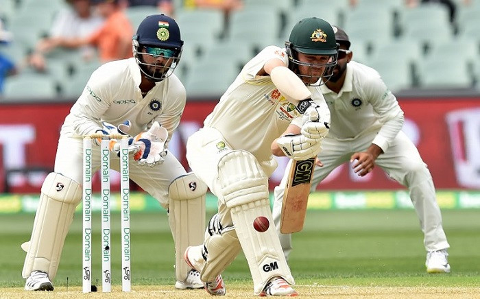 Australia's batsman Travis Head plays a shot as Indian wicketkeeper Rishabh Pant (L) looks on during day two of the first Test cricket match at the Adelaide Oval on 7 December 2018.  Picture: AFP