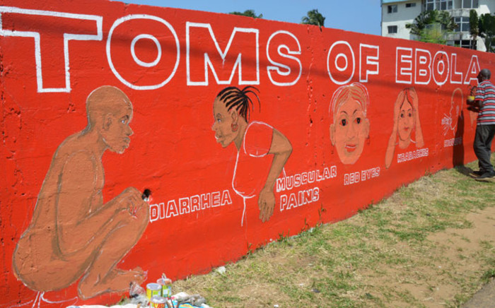 FILE: Liberian street artist Stephen Doe paints on 8 September, 2014 a mural to inform people about the symptoms of the deadly Ebola virus in Monrovia. Picture: AFP.
