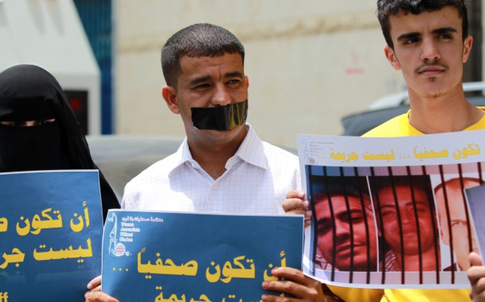 "Protesters hold placards in solidarity with Al-Jazeera journalists (seen on the poster) jailed in Egypt. The placard reads ""journalism is not a crime"". Picture: AFP."