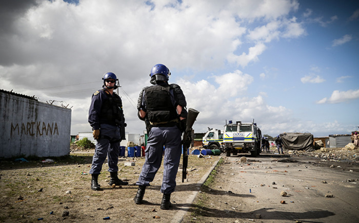 Law enforcement officials keep a watchful eye over vacant land in Philippi East following violent evictions in the area last week. Picture: EWN