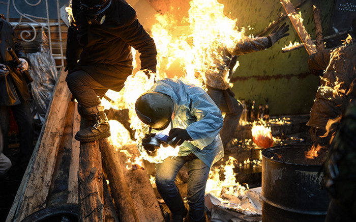 FILE: Protesters catch fire as they stand behind burning barricades during clashes with police on February 20, 2014 in Kiev. Picture: AFP.