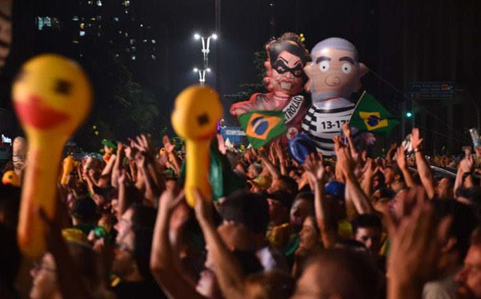 FILE. Supporters of the impeachment of Brazilian President Dilma Rousseff follow on big screens as lawmakers vote on whether the impeachment of Rousseff will move forward, in Sao Paulo, Brazil, on 17 April, 2016. Picture: AFP.