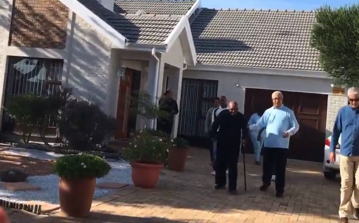 Archbishop Emeritus Desmond Tutu, dressed in black, is accompanied by IEC officials outside his house in Milnerton where he voted on 6 May 2019. Picture: Shamiela Fisher/EWN