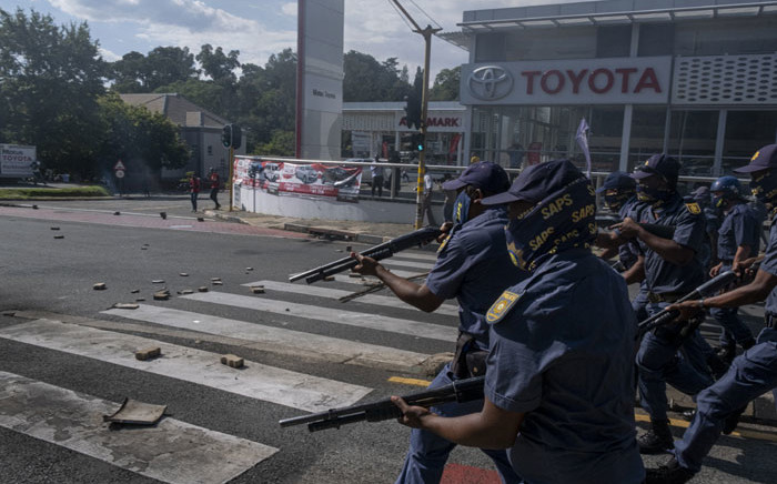 A large group of South African Police Service (SAPS) officers disperse a group of students who were blocking roads during a protest in Braamfontein, Johannesburg, on 10 March 2021. Picture: Emmanuel Croset/AFP