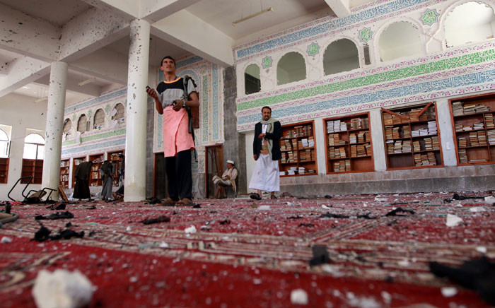 Yemeni armed men inspect the damage following a bomb explosion at the Badr mosque in southern Sanaa on 20 March, 2015. Picture: AFP