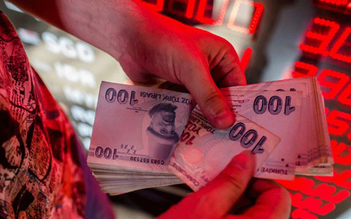 FILE: A money changer counts Turkish lira banknotes at a currency exchange office in Istanbul, on August 8, 2018. Picture: AFP.