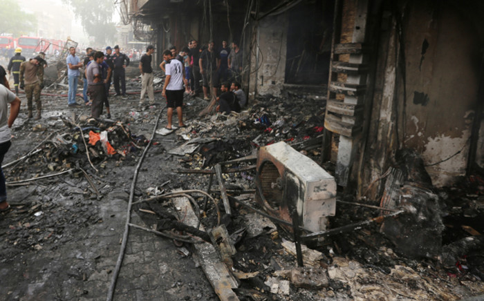 Iraqis inspect the damage at the site of a suicide car bombing claimed by the Islamic State group on 3 July, 2016 in Baghdad's central Karrada district. Picture: AFP.