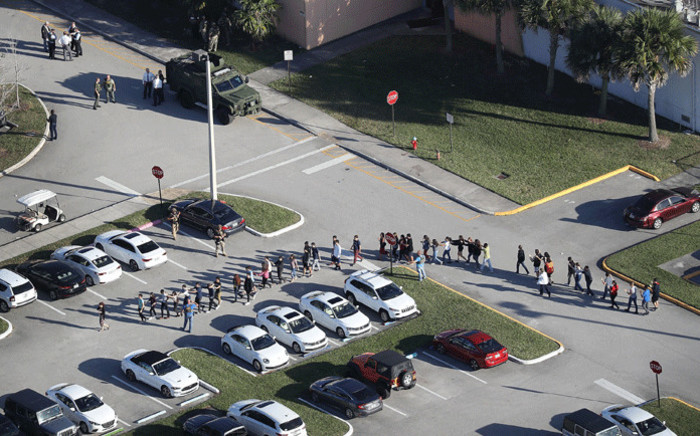 FILE: People are brought out of the Marjory Stoneman Douglas High School after a shooting at the school that reportedly killed and injured multiple people on 14 February, 2018 in Parkland, Florida. Picture: AFP