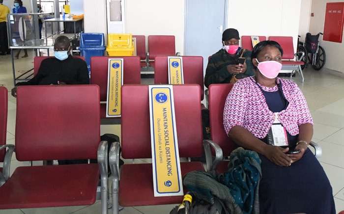 Kenyan passengers sit at the Jomo Kenyatta International Airport (JKIA), while observing social distancing as they wait to be checked in after the official launch on the resumption of local flights in Nairobi, on 15 July 2020. Picture: AFP