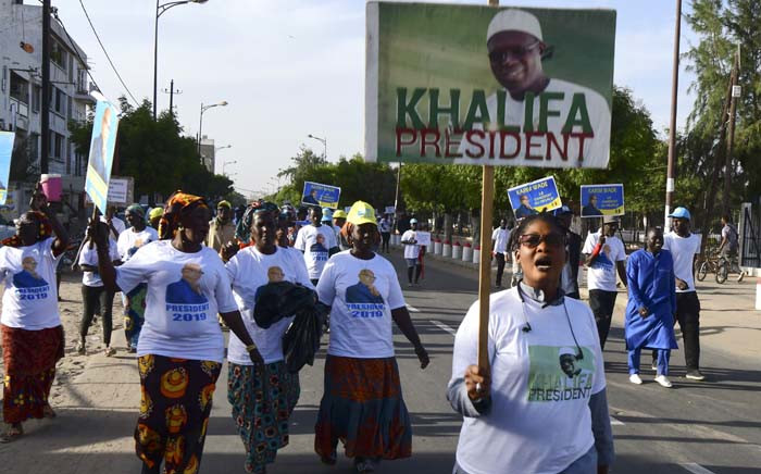 Senegal's opposition demonstrators hold pictures of the Mayor of Dakar Khalifa Sall and of former minister Karim Wade during a march to demand transparency in the 2019 elections, in Dakar, on 28 December 2018. Picture: AFP