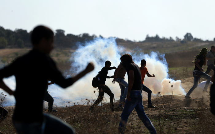 Palestinian protesters run for cover from teargas shot by Israeli soldiers during clashes near the border fence between Israel and the central Gaza Strip east of Bureij on 16 October 2015. Picture: AFP.